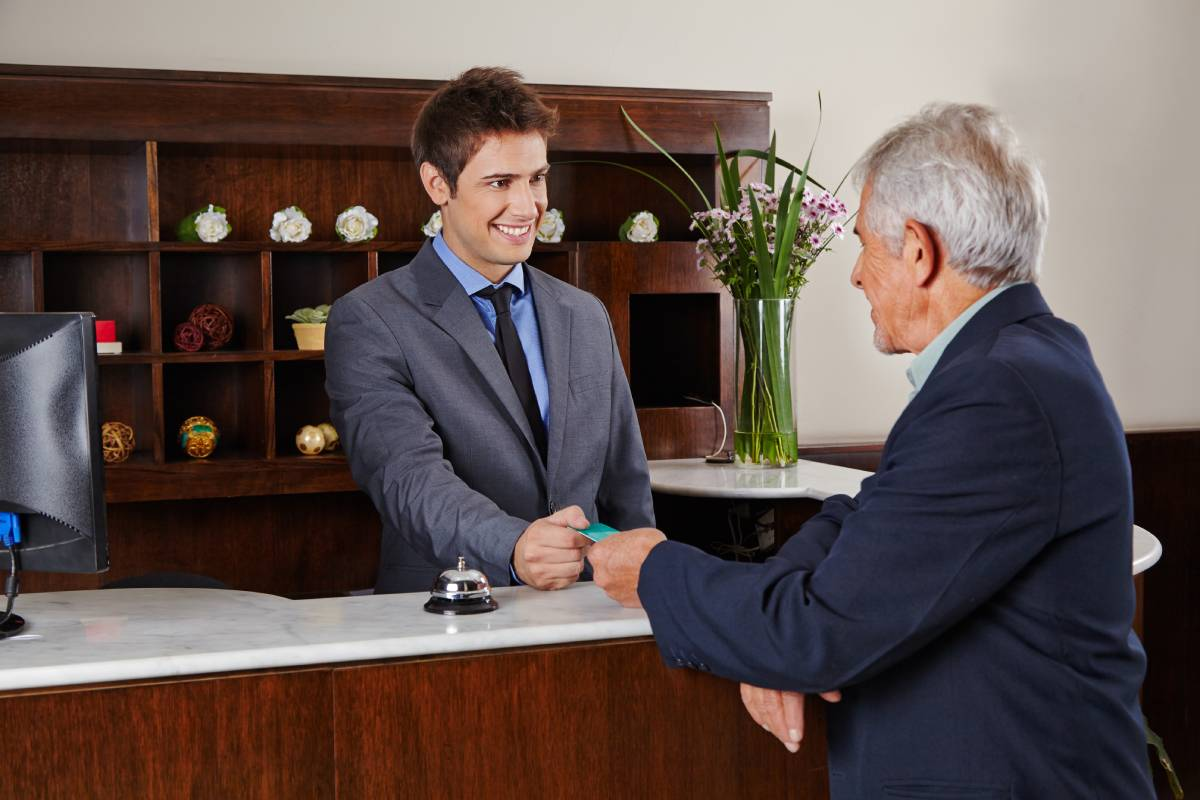 A hotel employee handing a key to a businessman