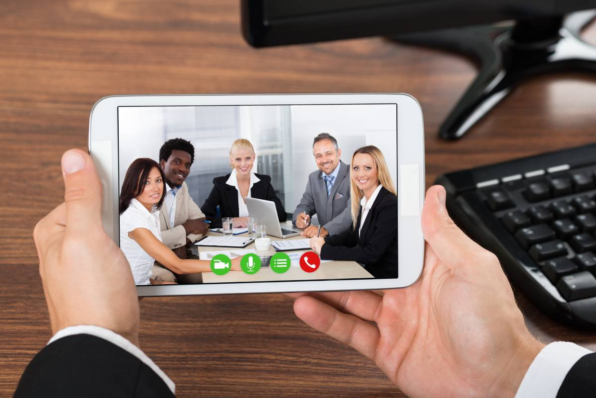 Businessman collaborating on video chat with team of business people