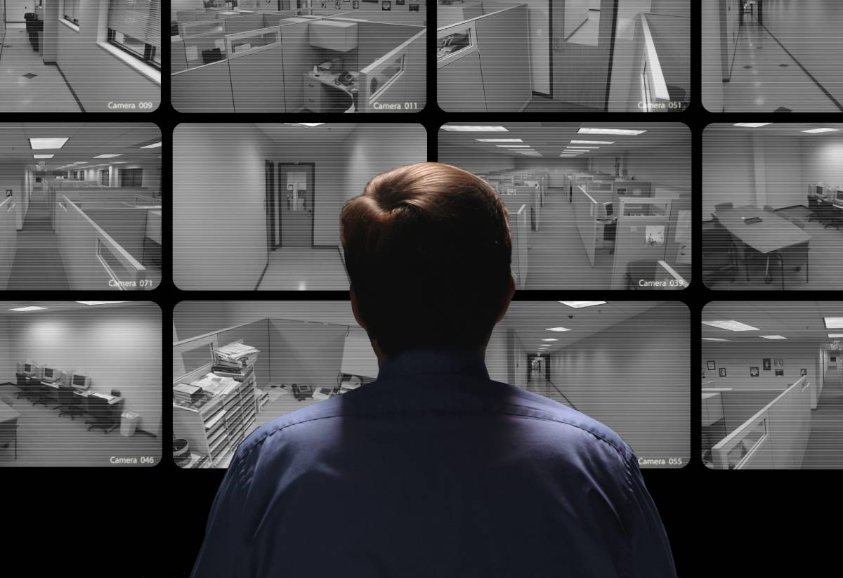 Man looking at different video surveillance screens
